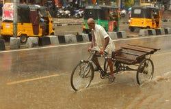Um homem pedals um riquexó de ciclo usado transportando bens durante uma inundação repentina fotos de stock royalty free