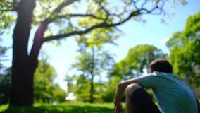 Um homem pensativo feliz do sonhador que anda no jardim e que senta-se para baixo na grama verde em um parque no dia de verão ens filme