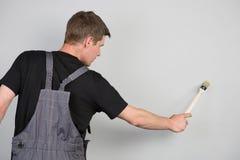 Um homem pinta a parede cinzenta com uma escova Imagem de Stock Royalty Free