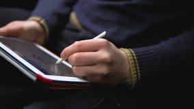 Um homem pinta uma imagem em uma tabuleta Fim acima vídeos de arquivo