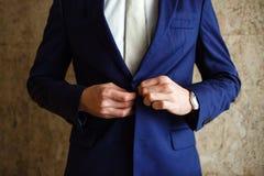 Um homem prende o casaco azul dos botões em sua mão seu relógio imagens de stock