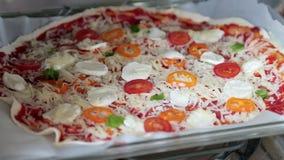 Um homem prepara a pizza e põe-na no forno video estoque