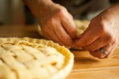 Um homem prepara tortas de maçã imagens de stock