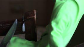 Um homem prepara uma colagem de cola Epoxy do dois-componente para reparar a cadeira Põe a colagem que cola no lugar e pressiona filme