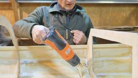 Um homem processa as emendas do barco, ele aquece-se com um hairdryer Isto é feito para a tensão Fazendo um navio à mão filme