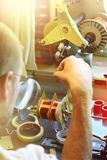 Um homem produzindo uma bobina de cobre elétrica para o transporte de alta tensão Imagens de Stock Royalty Free