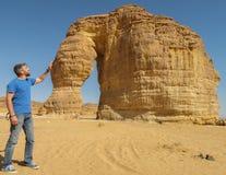 Um homem que afaga a formação de rocha conhecida como a rocha do elefante em Al Ula, saudita Arabi KSA foto de stock