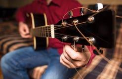 Um homem que ajusta uma guitarra imagens de stock