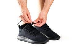 Um homem que amarra seus laços em sapatas pretas dos esportes Para esportes Iso fotos de stock