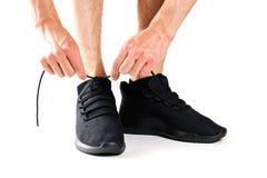 Um homem que amarra seus laços em sapatas pretas dos esportes Para esportes Iso imagem de stock royalty free