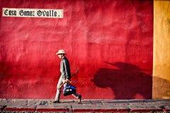 Um homem que anda ao longo da parede colorida com sua sombra Imagens de Stock Royalty Free
