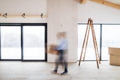 Um homem que anda com caixas de cartão ao fornecer a casa nova Borrão de movimento imagem de stock royalty free