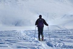 Um homem que anda com esqui fotos de stock