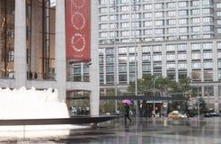 Um homem que anda com um guarda-chuva cor-de-rosa em torno do quadrado de Lincoln Center em New York City Fotos de Stock Royalty Free