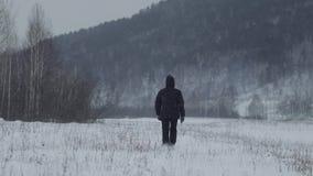 Um homem que anda em um campo nevado Vista traseira na pessoa em um campo nevado video estoque