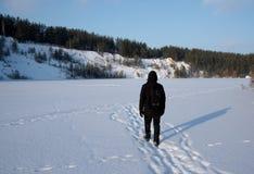 Um homem que anda na neve Silhueta de um homem que anda em uma planície nevado foto de stock royalty free