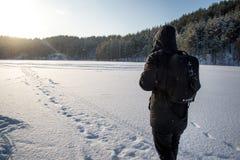 Um homem que anda na neve Silhueta de um homem que anda em uma planície nevado imagem de stock royalty free