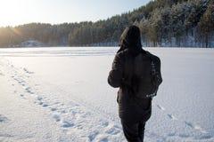 Um homem que anda na neve Silhueta de um homem que anda em uma planície nevado fotografia de stock