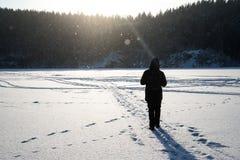 Um homem que anda na neve Silhueta de um homem que anda em uma planície nevado imagens de stock royalty free
