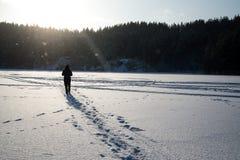 Um homem que anda na neve Silhueta de um homem que anda em uma planície nevado imagens de stock