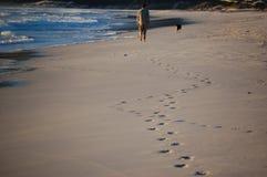 Um homem que anda seu cão ao longo da praia perto do oceano, deixando suas pegadas na areia imagem de stock