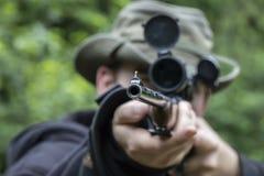 Um homem que aponta com um espaço em um rifle da caça fotografia de stock royalty free