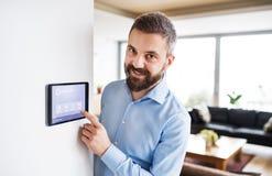 Um homem que aponta a uma tabuleta com a tela home esperta foto de stock