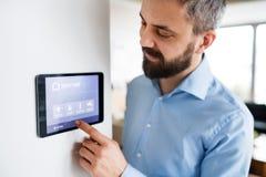 Um homem que aponta a uma tabuleta com a tela home esperta em casa foto de stock
