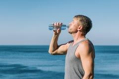 Um homem que bebe e derrama a água em sua cara da garrafa no oceano, refrescando após um exercício foto de stock