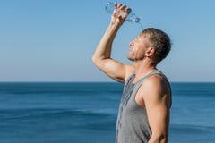 Um homem que bebe e derrama a água em sua cara da garrafa no oceano, refrescando após um exercício imagem de stock