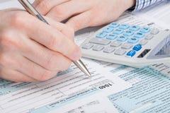 Um homem que completa EUA taxa o formulário 1040 com os dólares e a calculadora pura ele Fotos de Stock Royalty Free