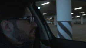 Um homem que conduz o carro no estacionamento do undergroung Fim acima Fundo de Bokeh filme