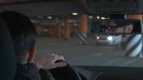 Um homem que conduz o carro no estacionamento do undergroung Fim acima Fundo de Bokeh video estoque
