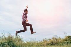 Um homem que corre e que salta com braços aumentou com energia Imagens de Stock