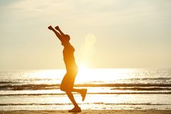 Um homem que corre na praia com os braços aumentados Foto de Stock