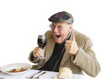 Um homem que dá os polegares acima da aprovaçã0 para o vinho e o alimento Fotos de Stock