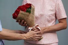 Um homem que dá um ramalhete das rosas a uma mulher imagens de stock royalty free