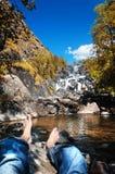 Um homem que descansa na cachoeira em montanhas de Altai, república de Uchar de Altai, Sibéria, Rússia imagens de stock