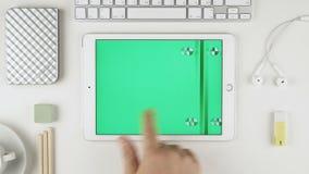 Um homem que desliza imagens verdes da chave do croma na exposição de ar do iPad de Apple em sua mesa vídeos de arquivo