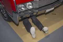 Um homem que encontra-se na terra sob o carro, executa o trabalho do reparo foto de stock