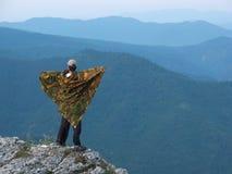 Um homem que está na borda de uma montanha imagens de stock