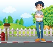 Um homem que está na rua perto da caixa postal de madeira Fotografia de Stock