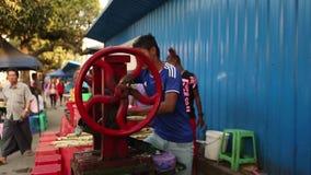 Um homem que extrai o suco açucarado do açúcar em Phnom Penh vídeos de arquivo