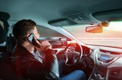 Um homem que fala em um telefone celular em um carro na alta velocidade Condução na alta velocidade Curso de carro fotografia de stock