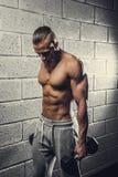 Um homem que faz exercícios do bíceps com pesos imagens de stock royalty free