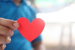 Um homem que guarda um coração vermelho em sua mão imagens de stock royalty free