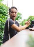 Um homem que guarda um móbil era chocado e o homem entusiasmado, superior senta o fotografia de stock royalty free