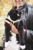Um homem que guarda o gato preto e branco ao andar no parque urbano fotografia de stock