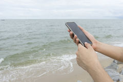 Um homem que guarda o telefone celular na praia imagem de stock royalty free