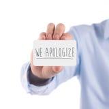 Um homem que guarda a placa nós desculpamo-nos cartão Fotografia de Stock